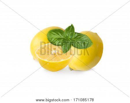 Two lemons and halves isolated on white background. Ripe lemons with basil close-up. Background citrus.