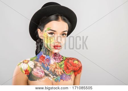 Attractive girl with dark long hair wearing black hat, body art paintings on neck, shoulders and face, painting flowers, make up model, copy space, portrait.