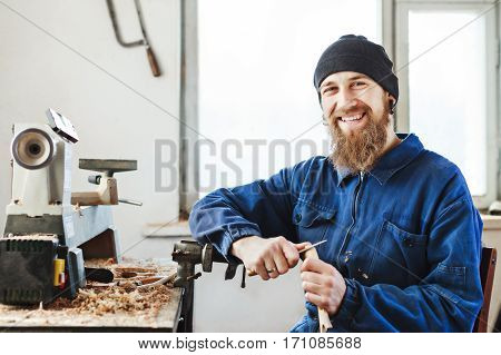 Smiling worker with a beard wearing blue jeans suit and black hat sitting on working place with wooden spoon, woodcarving instruments on table, window at background.