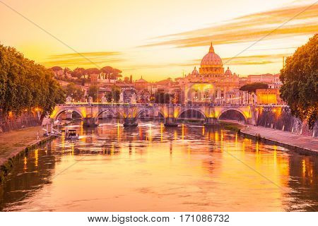 Sunset on Rome with San Pietro basilica, Sant'Angelo bridge and Tevere river in Roma, Italy