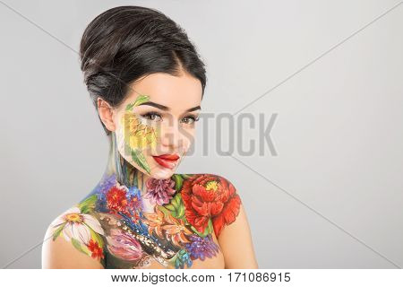Cute girl with dark hair, body art paintings on neck, shoulders and face looking at camera, painting flowers, make up model, copy space.