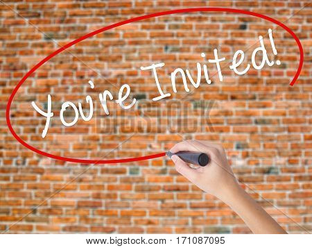Woman Hand Writing You're Invited! With Black Marker On Visual Screen