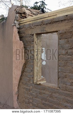 Adobe renovation showing bond beam, window header, and stucco layers.