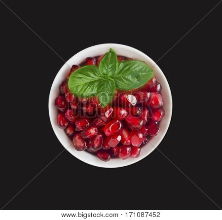 Pomegranate seeds isolated on black background. Red grains of a pomegranate in ceramic bowl. Sweet and juicy garnet with copy space for text. Top view.