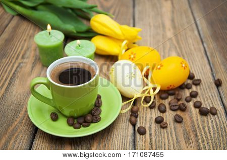 Aromatic coffee with yellow tulips Easter eggs and candles on wooden background