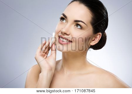 Smiling girl with black fixed hair behind and naked shoulders, cleaning face with cotton pad at gray studio background and looking left, portrait, close up.