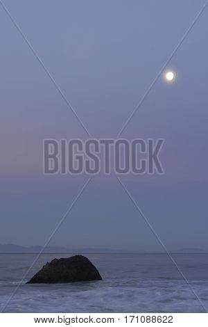 Pacific ocean in the morning light with a rock and the moon Vancouver Island Canada