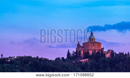 San Luca basilica church on Bologna hill, in a colorful sunset. pink and blue. in Italy