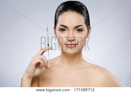 Beautiful girl with black fixed hair behind, dark big eyes and naked shoulders looking at camera, holding white syringe at gray studio background, portrait.