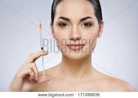 Beautiful brunette girl with fixed hair behind, dark big eyes and naked shoulders looking at camera and holding syringe, portrait, gray background.