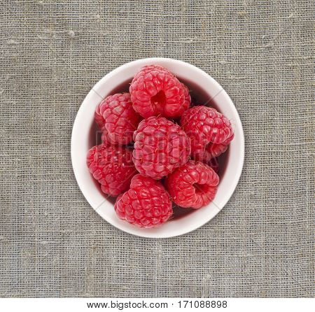 Raspberries in a white ceramic bowl. Ripe and tasty raspberries on a linen tablecloth. Top view.