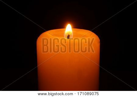 Small flame of burning candle in the darkness