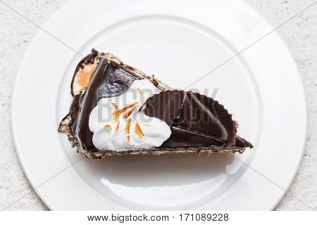 Dark chocolate cake slice with white cream, nuts and curl, close up