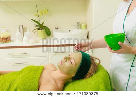 Beautician applying woman green algae mud mask on face in salon. Beauty relaxation skincare wellness in spa concept.