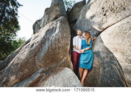 Cute couple standing together near rocks, outdoor. Beloved looking at each other, holding hands of each other and smiling. Girl wearing blue dress and man wearing white shirt and claret trousers. Full body