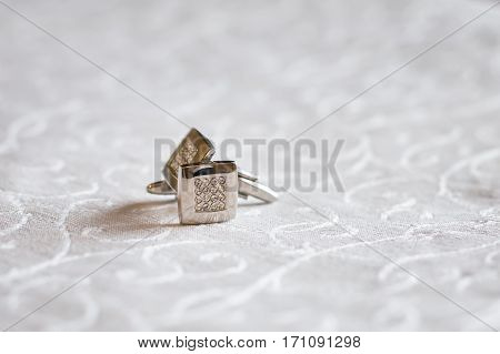 pair gold cufflinks on the white tablecloth