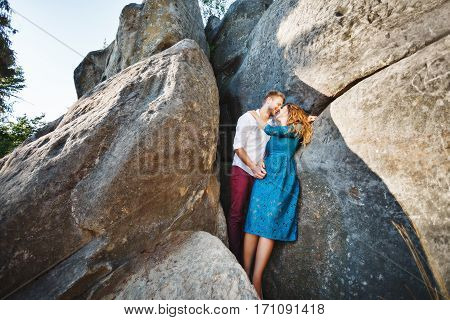 Nice couple standing together near rocks, outdoor. Beloved looking at each other, embracing and smiling. Girl wearing blue dress and man wearing white shirt and claret trousers. Faces very close to each other. Full body