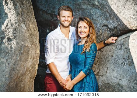 Cute couple standing together near rocks, outdoor. Beloved holding hands of each other, looking at camera and smiling broadly. Girl wearing blue dress and man wearing white shirt and claret trousers, he has stylish haircut