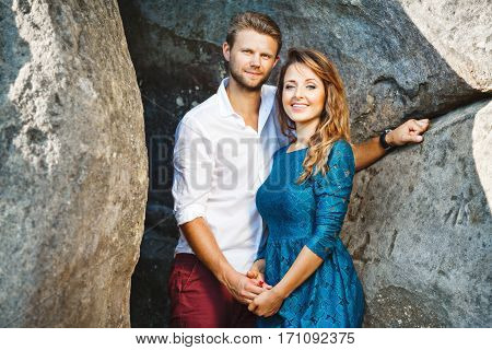 Cute couple standing together near rocks, outdoor. Beloved holding hands of each other, looking at camera and smiling. Girl wearing blue dress and man wearing white shirt and claret trousers, he has stylish haircut