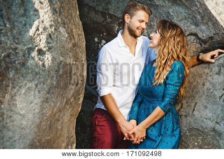 Cute couple standing together near rocks, outdoor. Beloved holding hands of each other, looking at each other and smiling. Profile. Girl wearing blue dress and man wearing white shirt and claret trousers, he has stylish haircut