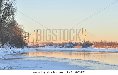 Coast of Neva River and Cable stayed bridge on the outskirts of St. Petersburg at sunny winter evening Russia.