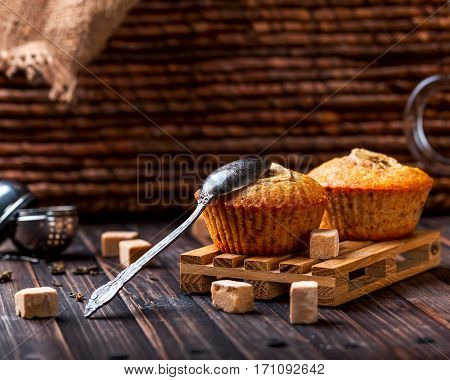 A couple of banana muffins on a wooden stand on a wooden background.Near to sugar lumps and spoon. Selective focus