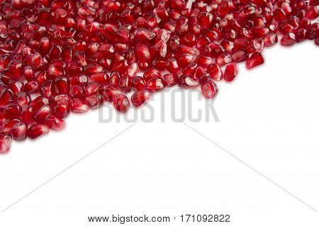 Background made of red pomegranate seeds. The scattered red grains of a pomegranate. Top view.