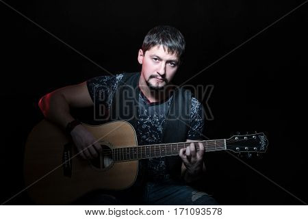 Portrait of handsome bearded man sitting in a chair with an acoustic guitar in hand, isolated on a black background