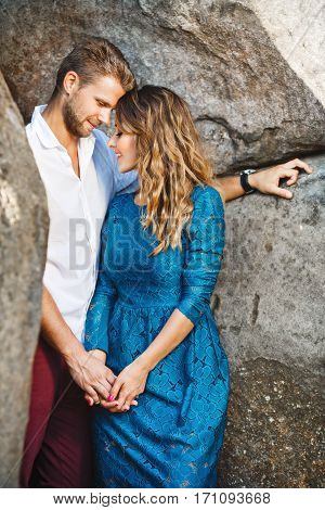 Nice couple standing together very close to each other between rocks, outdoor. Beloved holding hands of each other. Man looking down and she has closed eyes. Profile. Girl wearing blue dress and man wearing white shirt and claret trousers, he has stylish