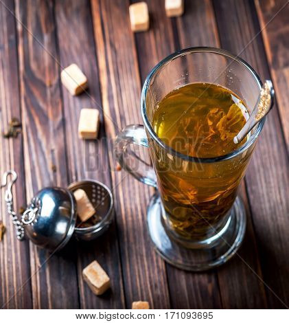 Green tea in a transparent mug. The Cup of tea on wooden background. Pieces of sugar near. Selective focus
