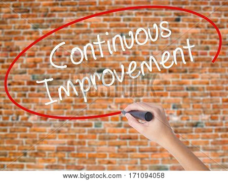 Woman Hand Writing Continuous Improvement With Black Marker On Visual Screen