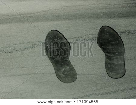 A pair of grown up footprints embedded in stone
