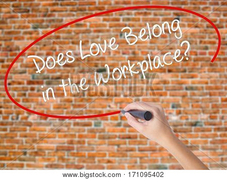 Woman Hand Writing Does Love Belong In The Workplace? With Black Marker On Visual Screen