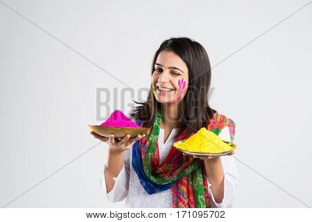 Pretty young indian girl holding powder colours in plate on the festival of colours called Holi, a popular hindu festival celebrated across india, isolated over white background, selective focus