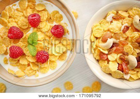 Tasty cornflakes with raspberries, raisins and nuts on table