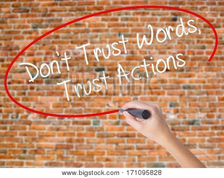 Woman Hand Writing Don't Trust Words, Trust Actions With Black Marker On Visual Screen