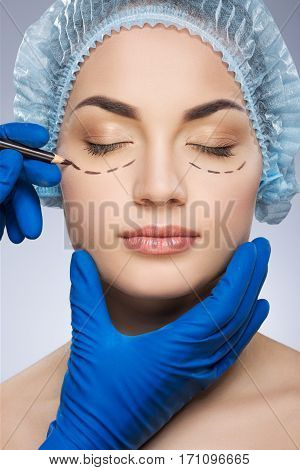 Plastic surgeon drawing dashed lines under eyes of girl. Hands in blue glove holding pencil and face. Girl with closed eyes in protective cap. Plastic surgery, beauty portrait, half face