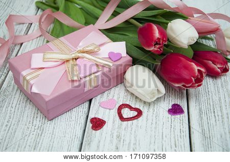 Gift box with colorful tulips with ribbon on a wooden background