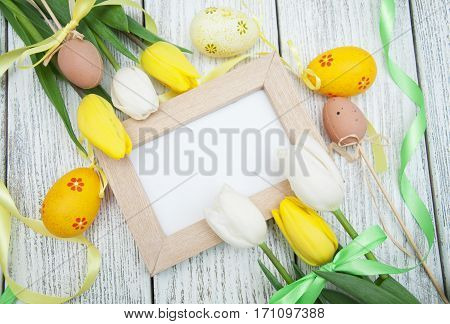 Tulips blank picture frame easter eqqs and ribbon on a white wooden background. Top view with copy space