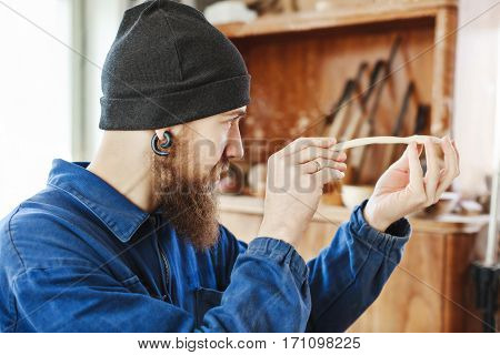 Worker with a beard wearing blue jeans suit and black hat holding and looking at wooden spoon, woodcarving, portrait, copy space.