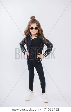 Portrait of little hipster girl in sunglasses. Posing. Curly modern hairstyle. Studio
