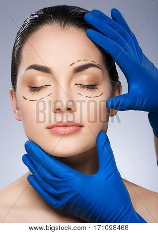 Dashed lines around eyes of girl. Beautiful girl with closed eyes. Hands of surgeon in blue gloves holding her face. Plastic surgery, beauty portrait