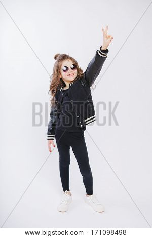 Portrait of little hipster girl in sunglasses. Posing. Curly modern hairstyle. Showing peace by fingers. Smiling. Studio