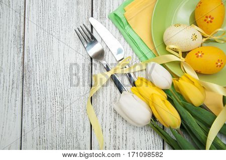Easter background with yellow tulips and colorful eggs over white wooden table. Top view with copy space