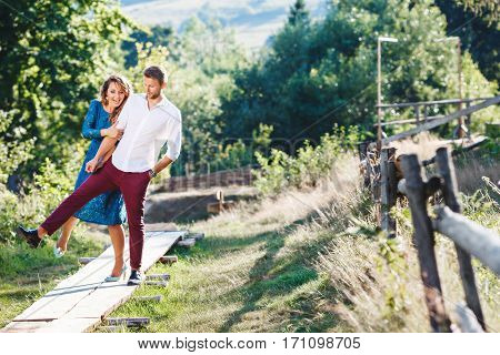 Nice couple walking together, outdoor, in the countryside. Beloved raised right leg. They looking down and smiling. Woman wearing blue dress and light blue shoes and man wearing white shirt, claret trousers and black shoes. Girl holding man's hand. Full b