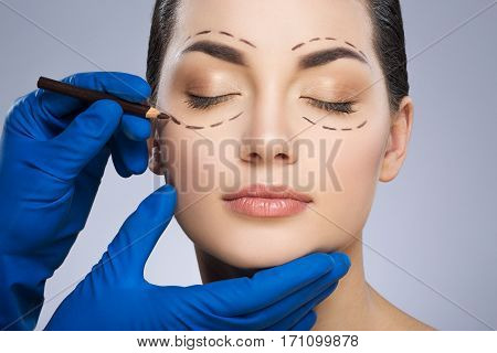 Plastic surgeon drawing dashed lines around closed eyes of girl. Hands in blue glove holding pencil and face. Perfect face. Plastic surgery, beauty portrait, closeup