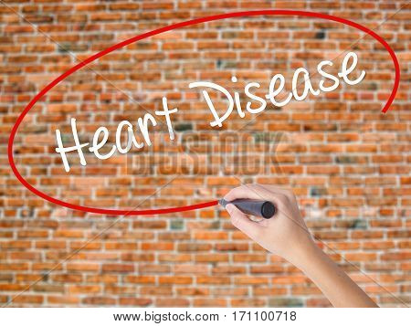 Woman Hand Writing Heart Disease With Black Marker On Visual Screen