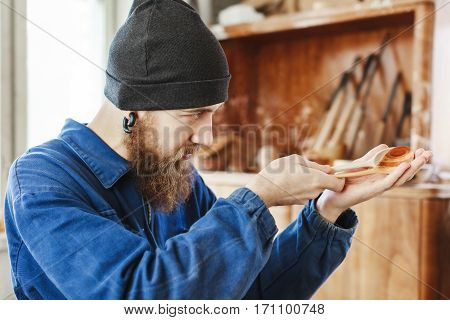 A portrait of man with a beard wearing blue jeans suit and black hat holding and looking at wooden spoon, woodcarving, portrait, copy space.