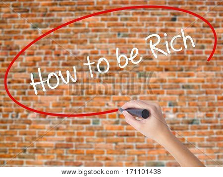 Woman Hand Writing How To Be Rich  With Black Marker On Visual Screen