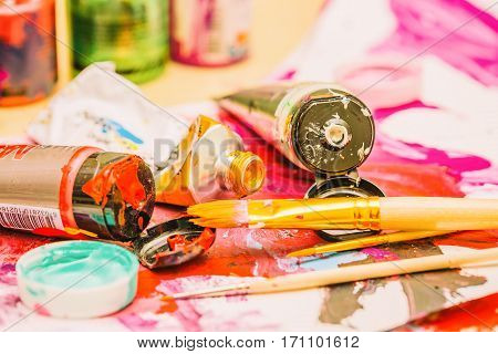 Painter workplace with tubes of multicolor oil paint and paintbrushes on painted paper close up.